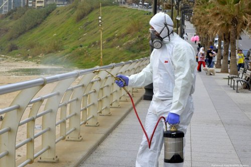 A health official wearing protective suit sprays disinfectant at fences on the coast as a precaution against the coronavirus (Covid-19) in Beirut, Lebanon on 5 March 2020 [Hussam Chbaro/Anadolu Agency]