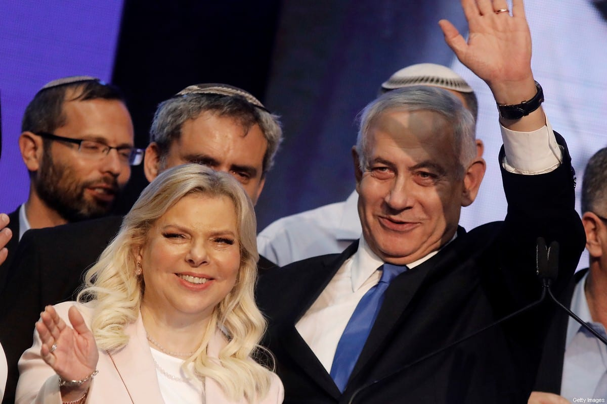 Israeli Prime Minister Benjamin Netanyahu (R) waves to supporters alongside his wife Sara Netanyahu at his Likud party's electoral campaign headquarters in the coastal city of Tel Aviv early on September 18, 2019. - [MENAHEM KAHANA/AFP via Getty Images]