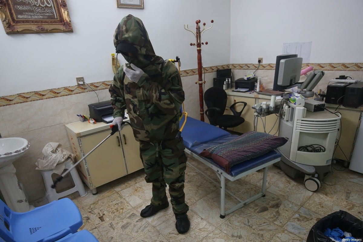 A member of the Iraqi Civil Defense disinfects a medical clinic in the northern Baghdad neighbourhood of al-Shuala on March 17, 2020 as a precaution against the coronavirus outbreak. [AHMAD AL-RUBAYE/AFP via Getty Images]