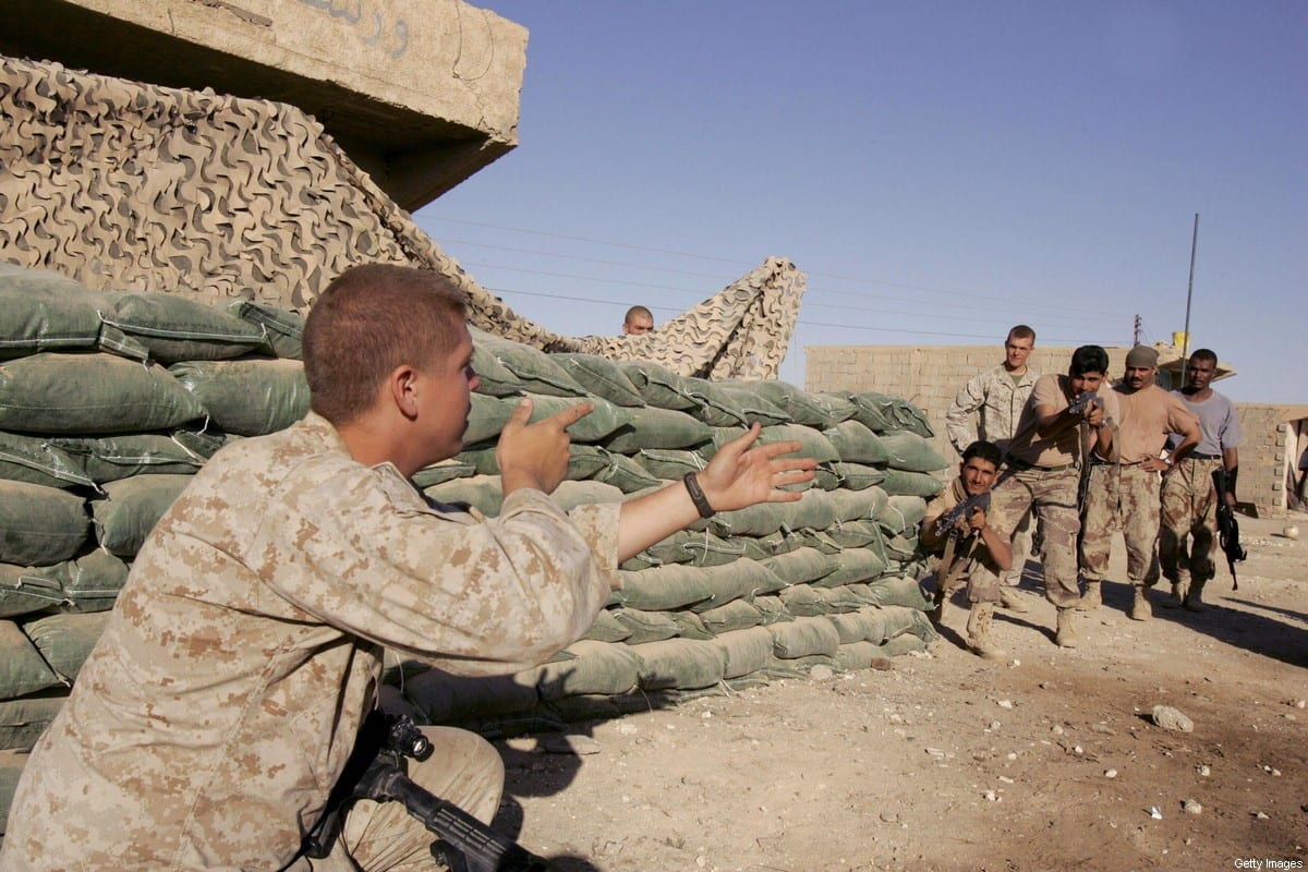 A US marine with 3/6 Marines trains Iraqi soldiers on urban combat techniques near the town of al-Qaim at the Iraqi-Syrian border, in western Iraq, 26 October 2006. [PATRICK BAZ/AFP via Getty Images]
