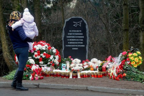 A woman with a baby mourns in front of the foundation stone for a Garden of Memory commemorating the 224 people killed in the bombing of a Russian airliner over Egypt on October 31, 2016 in the town of Vsevolozhsk outside Saint Petersburg [OLGA MALTSEVA/AFP via Getty Images]