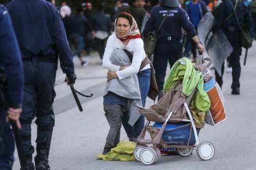 A woman protects her child as Greek riot police attack migrants on 3 March 2020 [Ayhan Mehmet/Anadolu Agency]