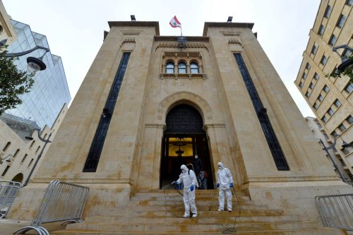 Health officials wearing protective suit sprays disinfectant outside of the Lebanese Parliament building as a precaution against the coronavirus in Beirut, Lebanon on 10 March 2020 [Hussam Chbaro/Anadolu Agency]