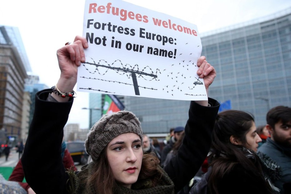 A woman holds a banner reading 'Refugees welcome, Fortress Europe: Not in our name!' during a protest against Greece's use of force, and EU's migration policies in Brussels, Belgium on 4 March 2020 [Dursun Aydemir/Anadolu Agency]