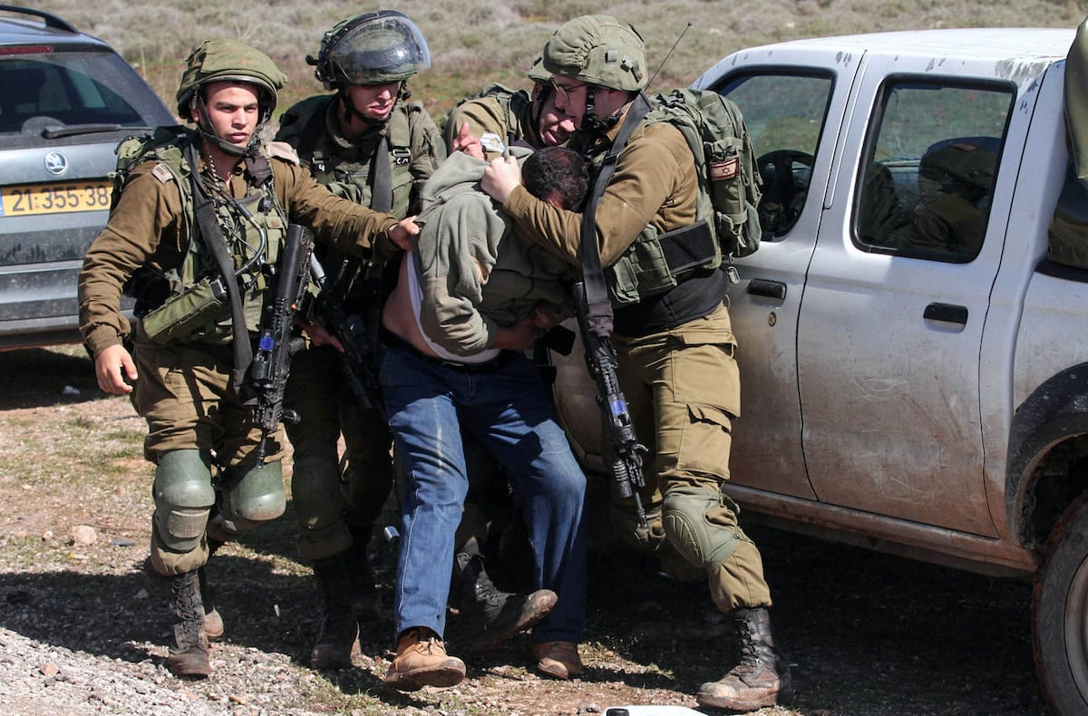 Israeli soldiers arrest a Palestinian protester during protest against bulldozing operations carried out by the occupation bulldozers near the village of Aqraba, south of the West Bank city of Nablus on 3 March 2020. [Ayman Nobani/ WAFA]