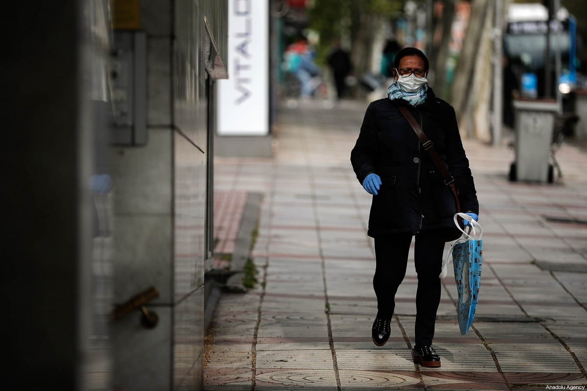 A man wearing a medical face mask walks down a sidewalk during the state of emergency by the government against the coronavirus (Covid-19) outbreak in Madrid, Spain on April 04, 2020 [Burak Akbulut / Anadolu Agency]