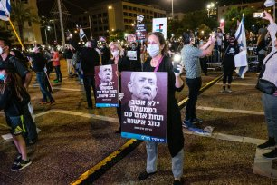 Israelis, wearing protective face masks due to the novel coronavirus (COVID-19) pandemic and keeping social distance, gather to protest against Prime Minister Benjamin Netanyahu at Rabin Square in Tel Aviv on 19 April 2020 [Nir Keidar/Anadolu Agency]