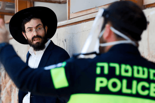 Israeli police officer speaks to a Strictly Orthodox student in Bnei Brak on Thursday afternoon [JACK GUEZ/AFP/Getty Images]