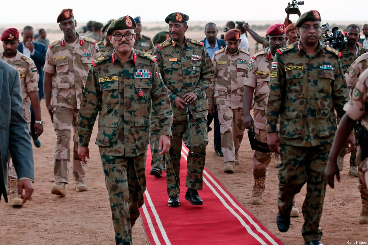 President of the Sudanese Transitional Council, General Abdel Fattah al-Burhan (C), walks alongside military officer during an army exercise on the outskirts of the capital Khartoum on 30 October 2019. [ASHRAF SHAZLY/AFP via Getty Images]