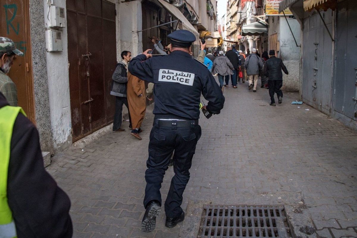 A Moroccan policeman, patrolling as part of a larger combined security force, chases after people to instruct them to return to and remain at home as a measure against the COVID-19 coronavirus pandemic in the capital Rabat's district of Takadoum on 27 March, 2020 [FADEL SENNA/AFP via Getty Images]