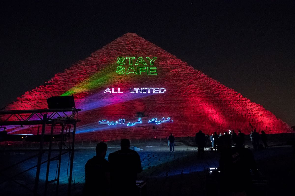 """People take pictures of the Great pyramid of Kheops at the Giza plateau outside the Egyptian capital Cairo where a laser projection writes """"Stay home, all united"""" on 30 March 2020, amid the spread of the COVID-19 infection, caused by the novel coronavirus. [KHALED DESOUKI/AFP via Getty Images]"""