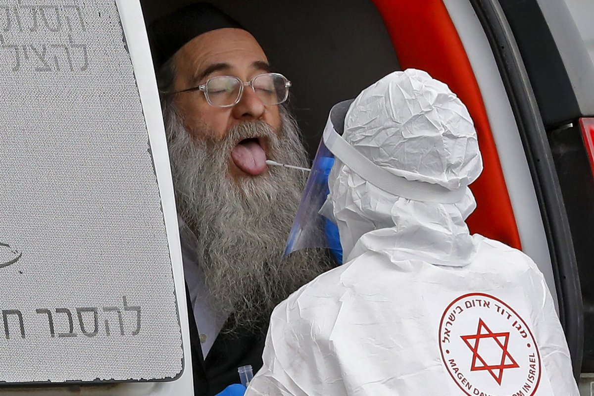 Israeli medical personnel from the Magen David Adom (MDA) national emergency service swab a resident from the city of Bnei Brak at their complex for COVID-19 testing in the city of Ramat Gan on March 31, 2020, [JACK GUEZ/AFP via Getty Images]