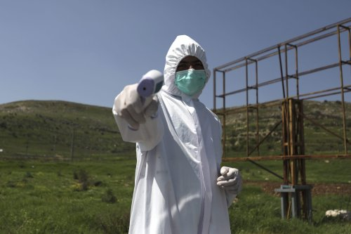 A Palestinian volunteer wearing a protective suit measures the temperature of people entering the village of Ain Yabrud near Ramallah controls amid the COVID-19 pandemic, on 6 April, 2020 [ABBAS MOMANI/AFP via Getty Images]