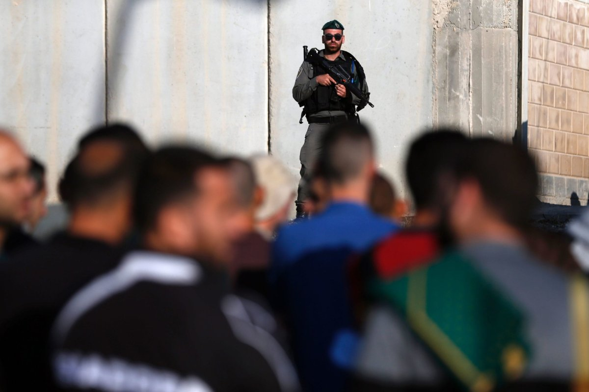 Israeli security forces stand guard as Palestinians wait to cross the Qalandia checkpoint between the West Bank city of Ramallah and Jerusalem on 2 June, 2017 [ABBAS MOMANI/AFP via Getty Images]