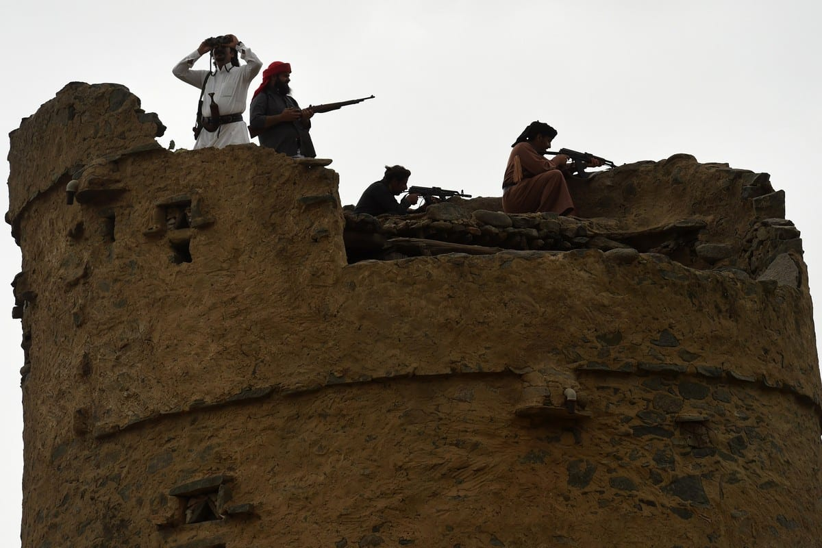 Fighters stand atop an ancient tower in the Jizan province, near the Saudi-Yemeni border, on 14 April 2015 [FAYEZ NURELDINE/AFP/Getty Images]