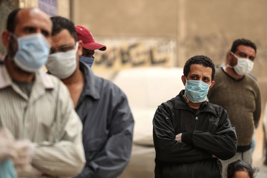 Egyptian men wearing masks wait outside a centre of non-governmental organisation Egyptian Food Bank to receive cartons with food aid on 5 April 2020 [MOHAMED EL-SHAHED/AFP/Getty Images)]