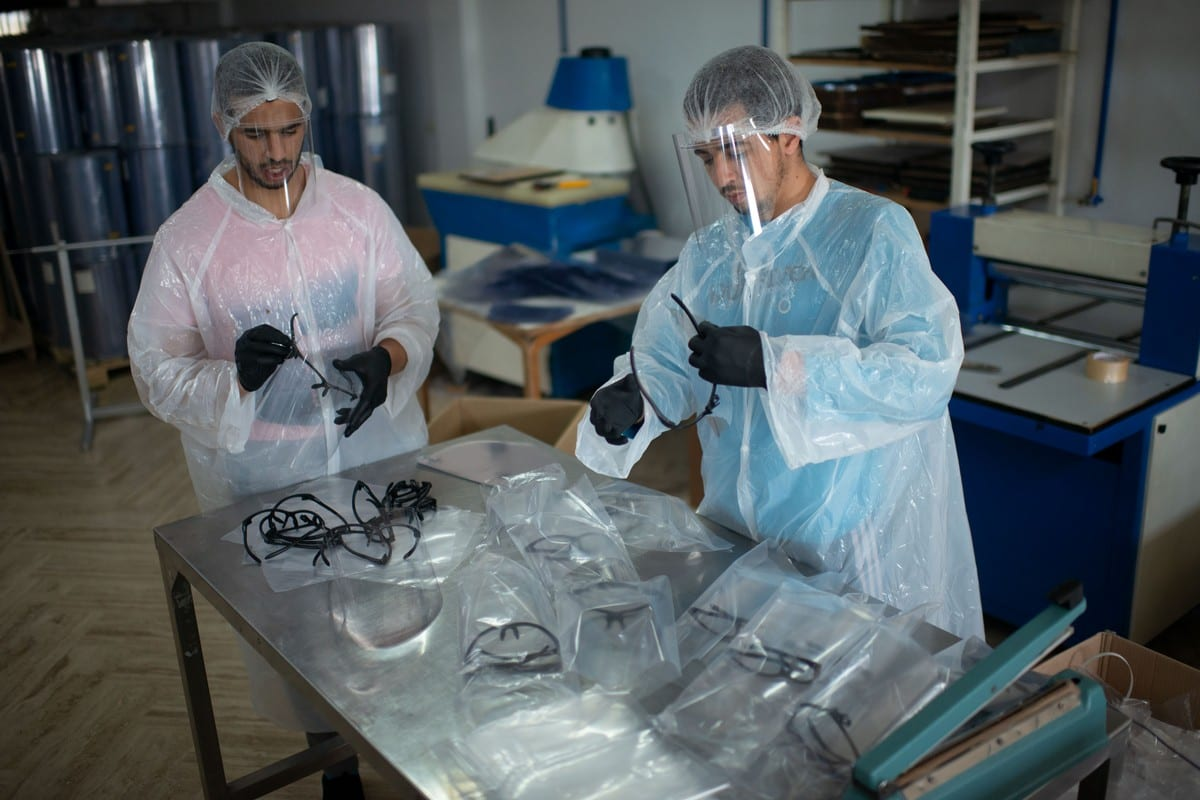 Workers in disposable clothing produce masks within the fight against the coronavirus (COVID-19) pandemic in Rabat, Morocco on 4 April 2020 [Jalal Morchidi/Anadolu Agency]