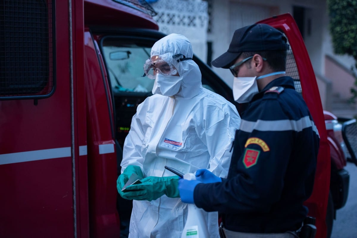 A medical worker wearing protective suit prepares to transport a suspected case of the new type of coronavirus (COVID-19) in Rabat, Morocco on 1 April 2020 [Jalal Morchidi/Anadolu Agency]