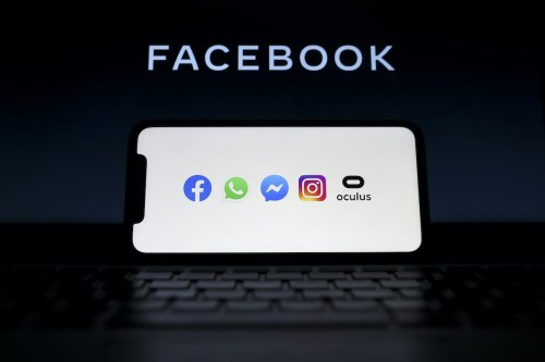 ANKARA, TURKEY - MAY 4: In this illustration photo, logos of social media applications Facebook, WhatsApp, Instagram, Messenger and Oculus are seen on a mobile phone as Facebook logo is seen behind on a screen, in Ankara, Turkey on May 4, 2020. ( Hakan Nural - Anadolu Agency )