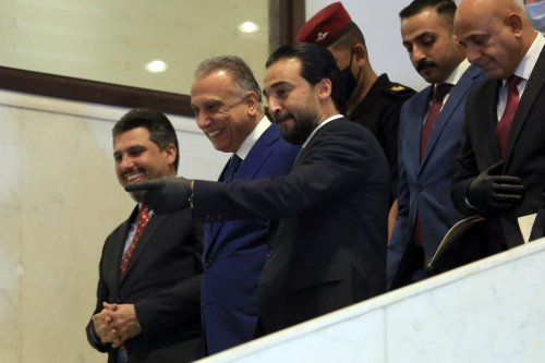 The speaker of the Council of Representatives of Iraq, Mohamed Al-Halbousi (right 3) welcomes Iraqi PM-designate Mustafa al-Kadhimi who arrived at the parliament for vote of confidence in Baghdad, Iraq on 6 May 2020. [Murtadha Al-Sudani - Anadolu Agency]