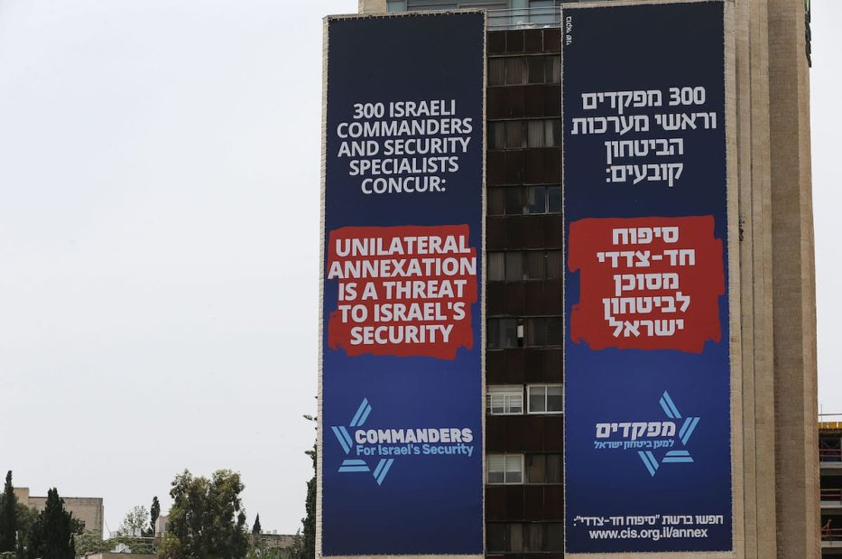 """Banners mounted on a building facade upon the visit of the U.S. Secretary of State Mike Pompeo to discuss illegal Jewish settlements and the """"annexation"""" of the Palestinian land, Jordan Valley located in the occupied West Bank, are seen on a street in Begin Boulevard in the West Jerusalem on 13 May 2020. [Mostafa Alkharouf - Anadolu Agency]"""