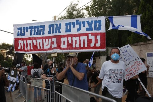 A group of activists stands holding opposition banners behind the barricade to demonstrate the coalition government formed by Israeli Prime Minister Benjamin Netanyahu and Blue and White Alliance leader Benny Gantz in West Jerusalem on 17 May 2020. [Mustafa Alkharouf - Anadolu Agency]