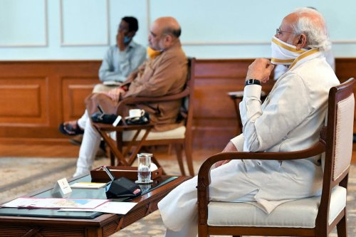 Indian Prime Minister Narendra Modi (R), wearing a face mask as as a preventive measure against the coronavirus (COVID-19) pandemic in New Delhi on 18 May 2020 [Indian Government/Anadolu Agency]