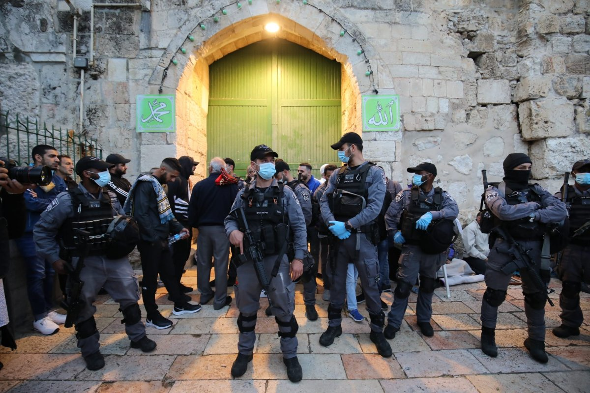 Israeli police stand guard in front of doors as Palestinian Muslims gather to perform Eid al-Fitr prayer at Al-Aqsa Mosque, which is closed as a precaution against the novel coronavirus (COVID-19) pandemic in Jerusalem on May 24, 2020. [Mostafa Alkharouf - Anadolu Agency]