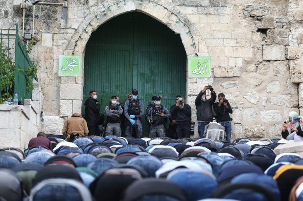 Israeli police stand guard in front of doors as Palestinian Muslims gather to perform Eid al-Fitr prayer at Al-Aqsa Mosque, which is closed as a precaution against the novel coronavirus (COVID-19) pandemic in Jerusalem on May 24, 2020. Eid al-Fitr is a religious holiday celebrated by Muslims around the world that marks the end of Ramadan, Islamic holy month of fasting. [Mostafa Alkharouf - Anadolu Agency]