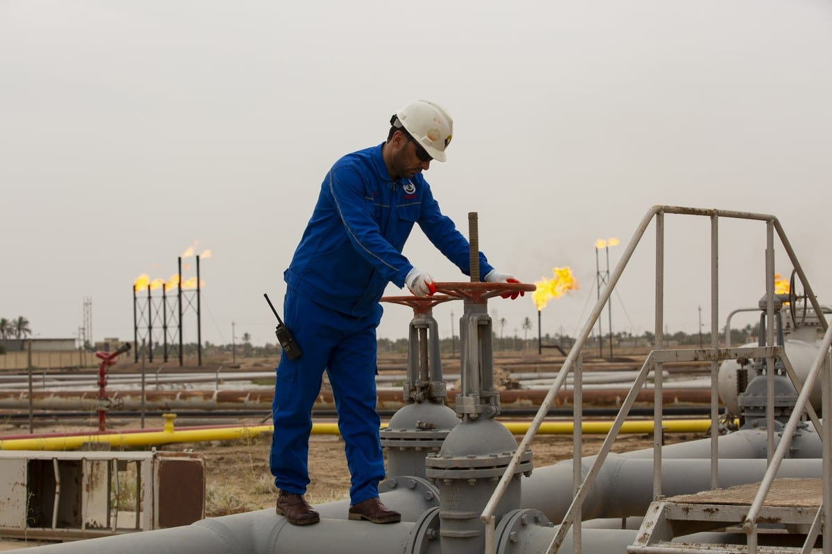 An employee turns a valve at a natural gas field in Iraq on 21 April 2020 [HUSSEIN FALEH/AFP/Getty Images]