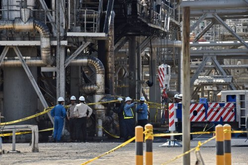 Employes of Aramco oil company stand near a heavily damaged installation in Saudi Arabia's Khurais oil processing plant on 20 September 2019. [FAYEZ NURELDINE/AFP via Getty Images]