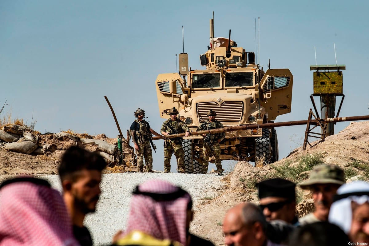 Syrian Kurds take part in a demonstration against Turkish threats at a US-led international coalition base on the outskirts of Ras al-Ain in Syria [DELIL SOULEIMAN/AFP via Getty Images]