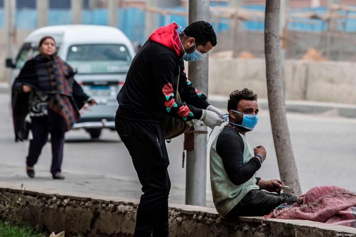 A volunteer (L) ties a mask onto an Egyptian woman in a street in the Egyptian capital Cairo on 20 March 2020 [KHALED DESOUKI/AFP/Getty Images]