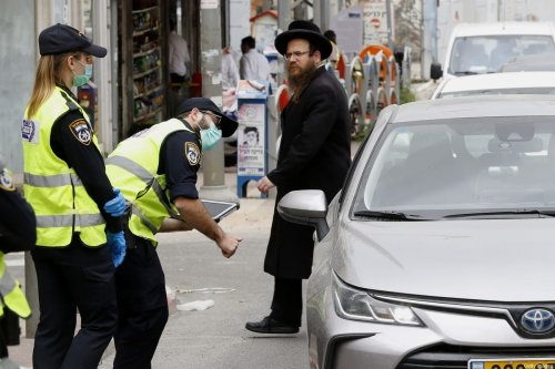 Israeli police talk to a driver at a checkpoint in the city of Bnei Brak, a city near Tel Aviv with a largely ultra-Orthodox population, on 31 March, 2020 [JACK GUEZ/AFP via Getty Images]