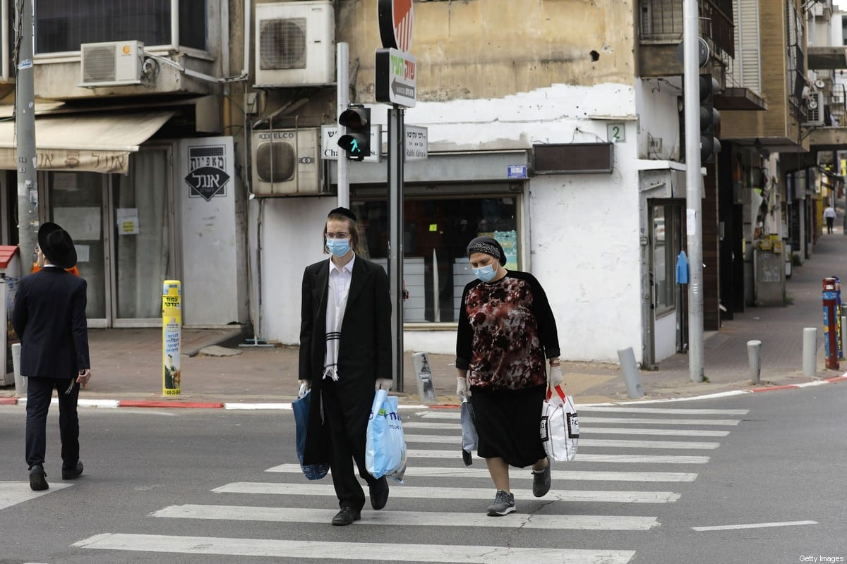 Ultra-Orthodox Jews wearing protective masks walk by carrying bags of shopping in the religious Israeli city of Bnei Brak, near Tel Aviv, on April 6, 2020 [MENAHEM KAHANA/AFP via Getty Images]