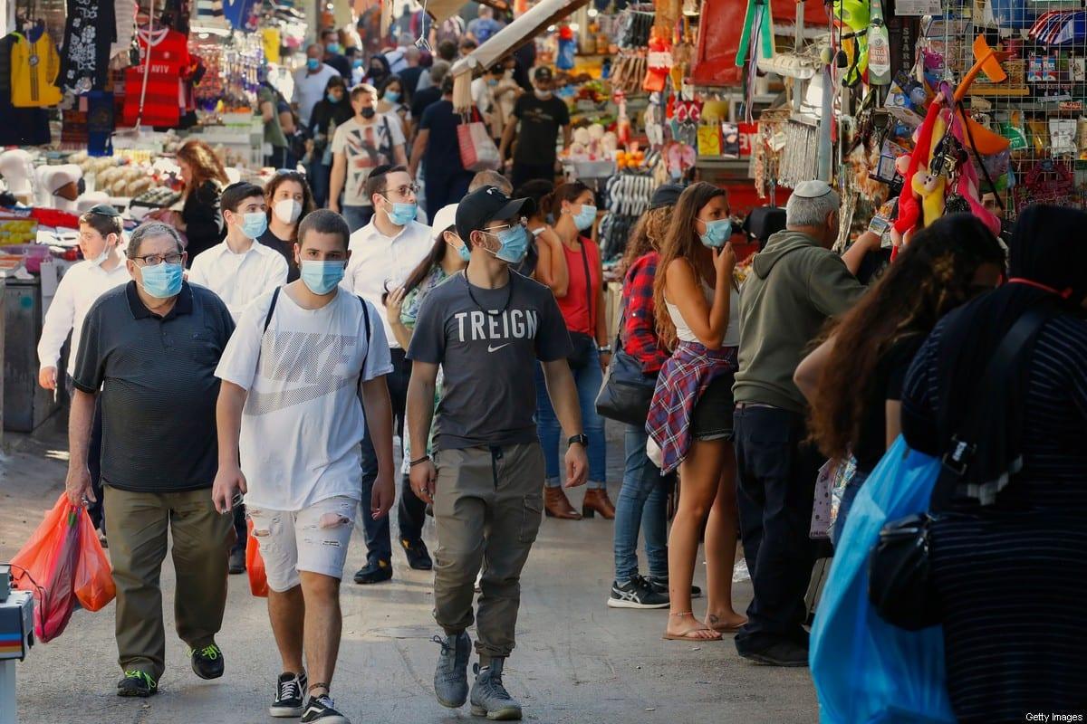 Shoppers wearing protective masks against the novel coronavirus, walk through the Shuk HaCarmel, or the Carmel market, in the Israeli coastal city of Tel Aviv on May 7, 2020 [JACK GUEZ/AFP via Getty Images]