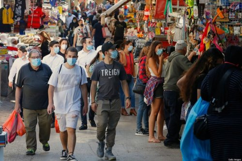 Shoppers wearing protective masks against the novel coronavirus, walk through the Shuk HaCarmel, or the Carmel market, in the Israeli coastal city of Tel Aviv on May 7, 2020 [JACK GUEZ/AFP via Getty Images]