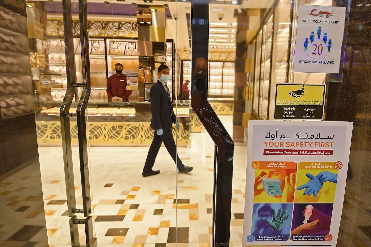 A man clad in face mask and latex gloves, due to the COVID-19 coronavirus pandemic, walks past jewellers' shops at the Dubai Gold Souk in the Gulf emirate on 13 May, 2020 [KARIM SAHIB/AFP via Getty Images]