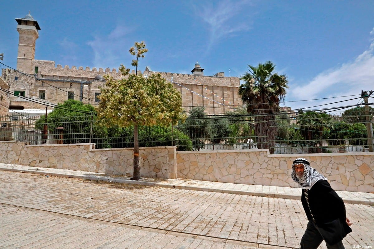 A Palestinian man walks past the Ibrahimi mosque in the occupied West Bank, on May 15, 2020 [HAZEM BADER/AFP/Getty Images]
