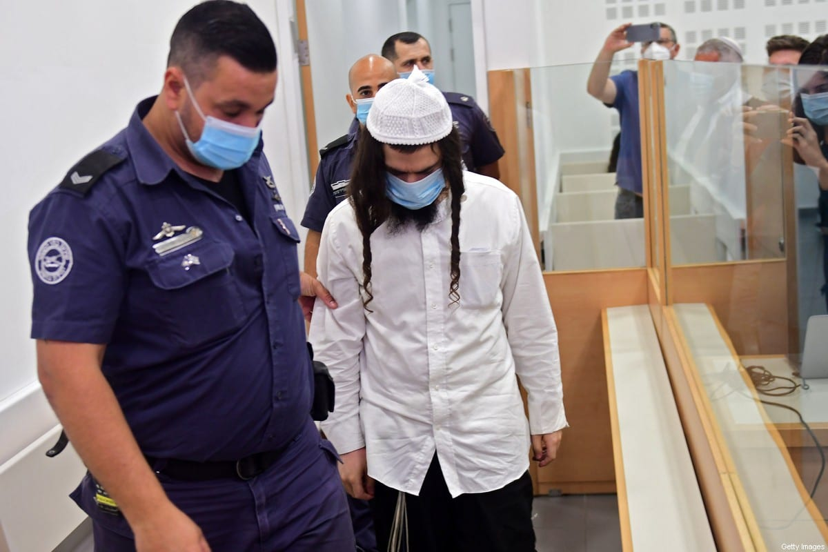 Amiram Ben-Uliel, a Jewish settler, is lead by police into court at the Central Lod District Court, in the central Israeli city on May 18, 2020, for his sentencing hearing over the 2015 arson attack that killed a Palestinian toddler and his parents. [AVSHALOM SASSONI/POOL/AFP via Getty Images]