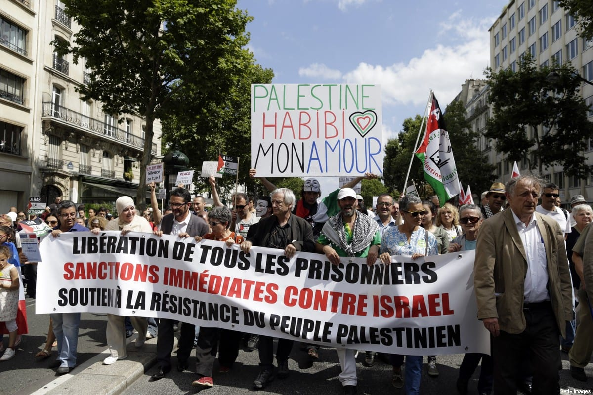 "Demonstrators hold a placard reading ""Palestine Habibi my love"" (top) during a demonstration against Israel's military operations in Gaza and in support of the Palestinian people, on 2 August, 2014 in Paris [KENZO TRIBOUILLARD/AFP via Getty Images]"