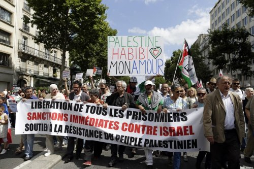 """Demonstrators hold a placard reading """"Palestine Habibi my love"""" (top) during a demonstration against Israel's military operations in Gaza and in support of the Palestinian people, on 2 August, 2014 in Paris [KENZO TRIBOUILLARD/AFP via Getty Images]"""