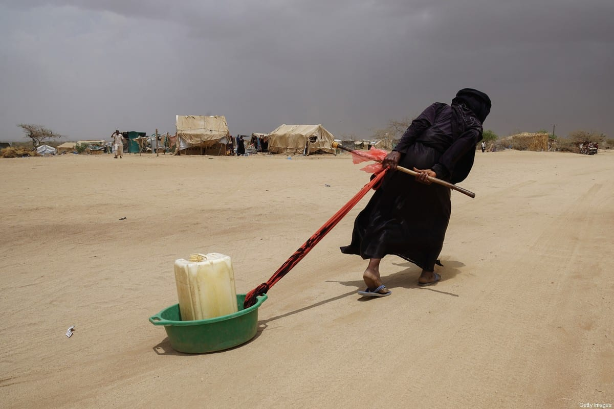 A displaced Yemeni woman drags water back to her tent in Abs IDP camp located just 40 KM from the frontline to Saudi Arabia [Giles Clarke, UN OCHA/Getty Images]