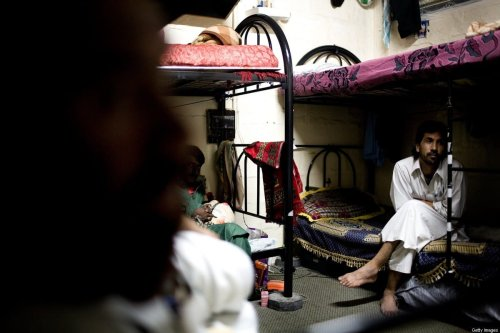 Migrant workers sit on bunk beds inside the labor camps July 18, 2008 on the outskirts of Abu Dhabi, United Arab Emirates. [Ghaith Abdul Ahad/Getty Images]