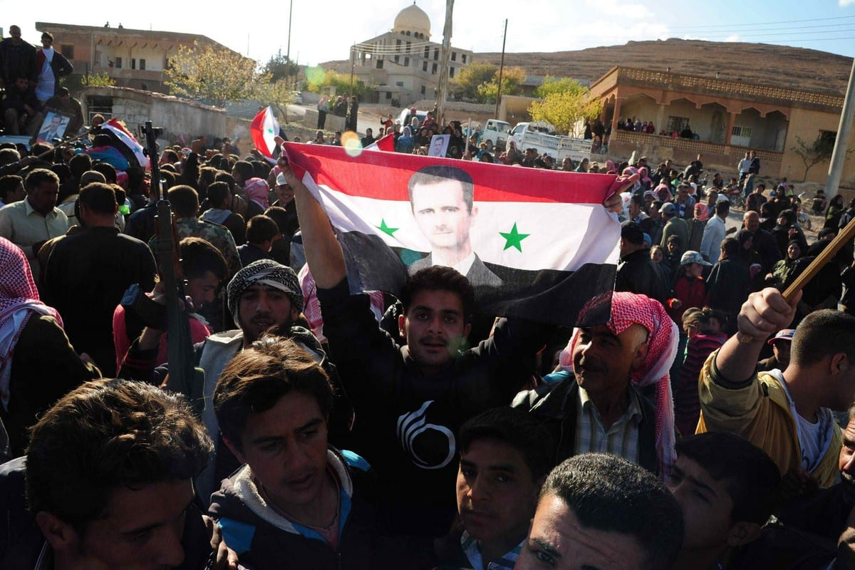 A Syrian man holds his national flag bearing a portrait of Syrian President Bashar Al-Assad in Maalula, Syria on 14 April 2014 [STR/AFP via Getty Images)