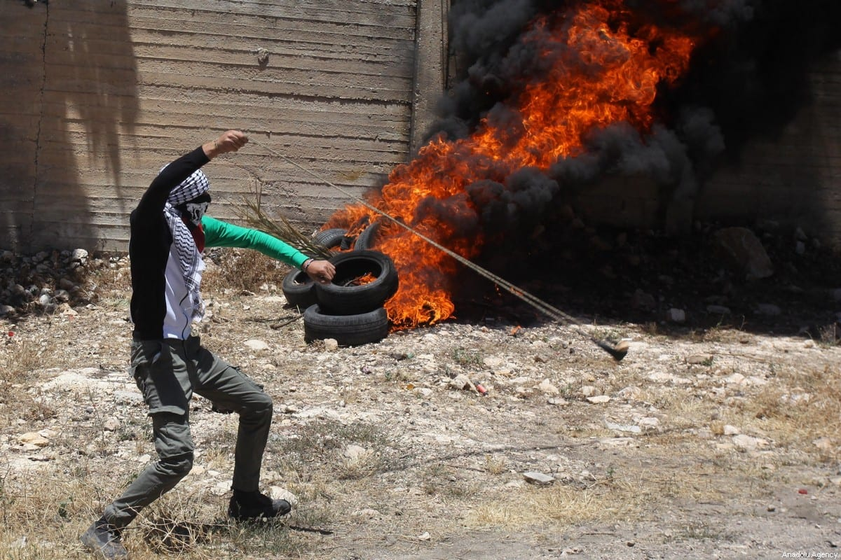 Palestinian demonstrators burn tyres and throw rocks in response to Israeli forces' intervention during a protest at Qafr Qaddum village against new Jewish settlements construction and discrimination wall, in Nablus, West Bank on 12 June, 2020 [Nedal Eshtayah/Anadolu Agency]