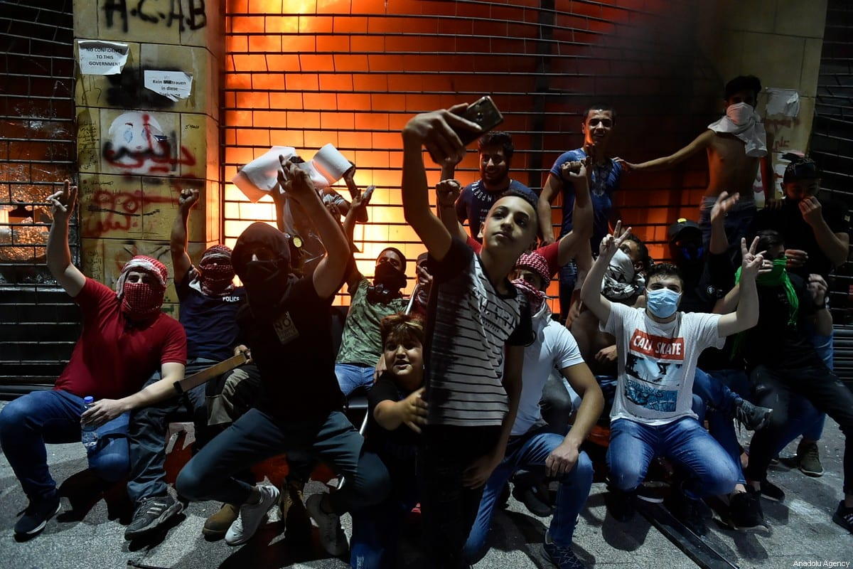Protesters gesture and take selfies in front of a store which was attacked by them during a demonstration against dire economic conditions and depreciation in the value of the Lebanese pound against the dollar due to the coronavirus (COVID-19) pandemic at the Riad al Solh Square in Beirut, Lebanon on June 12, 2020 [Hussam Shbaro - Anadolu Agency]