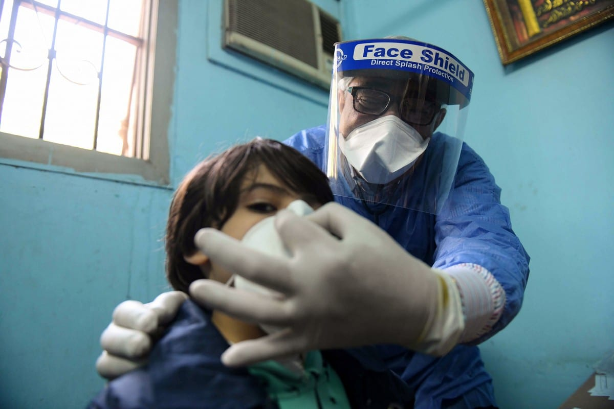 An Egyptian doctor adjusts the protective mask covering a young patient at a hospital in Cairo, Egypt on 19 on April 2020 [AHMED HASAN/AFP/Getty Images]