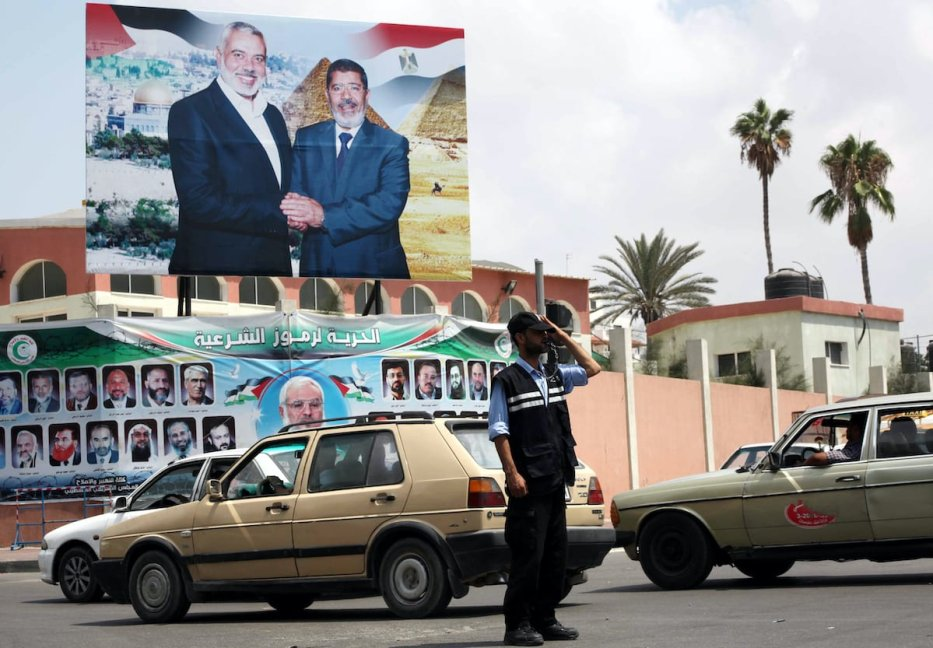 A Palestinian Hamas policeman organizes the traffic in front of a photograph released by Hamas, Egyptian President Mohammed Morsi, right, meets the Palestinian Prime Minister in Gaza, Ismail Haniyeh, in Gaza city on 29 August 2012. [Ashraf Amra/Apaimages]