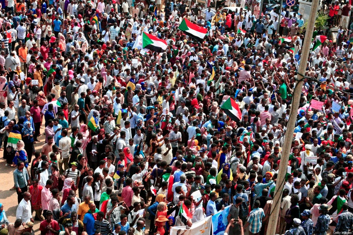 People wave Sudanese national flags as they rally at a mass demonstration near the presidential palace in the capital Khartoum on 12 September, 2019 [EBRAHIM HAMID/AFP via Getty Images]
